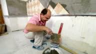 man installs ceramic tile video