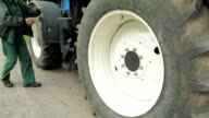 A man is about to sit in a big huge tires tractor video