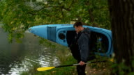 Man is carrying a blue kayak to the river shore and puts it on water. video