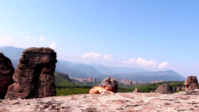 Man is climbing a rock and sitting to admire the beautiful Belogradchik valley video