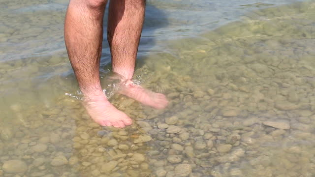 Man is cooling his feet in a lake video