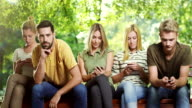 Man is getting bored while all his friends looking at phone video