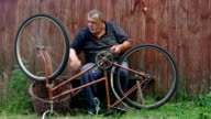 Man is nervous about very old bicycle to repair sitting against wooden fence video