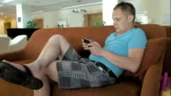 A man is on his mid pad tablet on a couch video