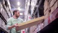 A man is putting boxes back on the shelves in a warehouse and going away from the camera video