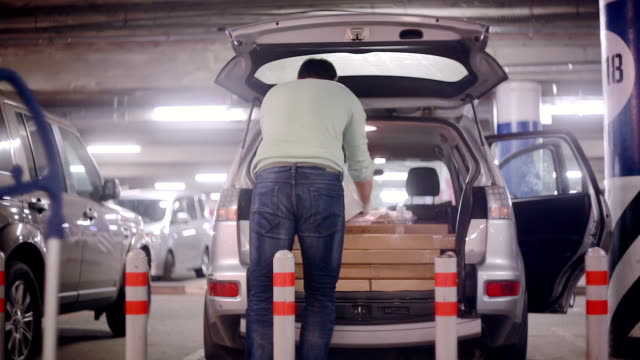 A man is putting purchase in the boot of a car after shopping standing in the underground parking lot near mall video
