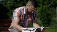 Man is reading sport magazine on wood bench. video