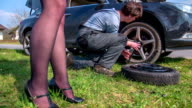 Man is screwing the tier beck on the car and a woman is standing net to him on the side of the road on a sunny day, footage is taken in slow motion. video