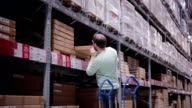 A man is taking a box from a shelf, putting it on the trolley in a warehouse video