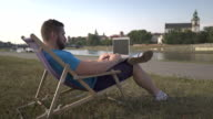 Man is typing on laptop, lying on sunbed by the river. video