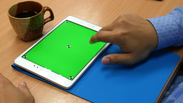 Man is using tablet with green screen on the wooden table video