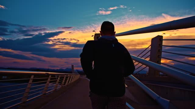 SLO MO Man Jogging Across A Bridge At Dusk video
