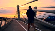 SLO MO Man Jogging Across A Bridge At Dusk video