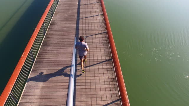AERIAL Man jogging across the bridge video