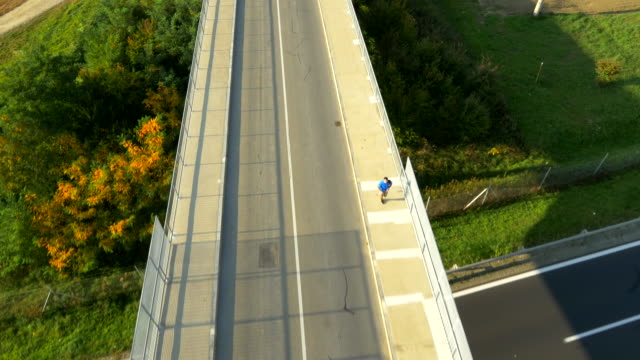 AERIAL Man Jogging Across The Overpass video
