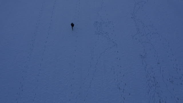 AERIAL Man Jogging Across The Snowy Field video