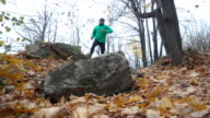 Man Jogging cross country And Jumping Over Obstacle running in forest and mountain. Training and exercising outdoors cross country running in autumn landscape. Sports Motivation. Slow Motion. video