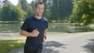 SLO MO TS Man jogging in the park along a lake video
