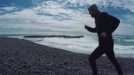 Man jogging on the rocky beach video