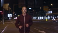 SLO MO TS Man jogging the city streets at night video