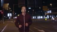 SLO MO TS Man jogging the city streets at night video