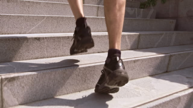 SLO MO TS Man jogging up stairs and alongside building video