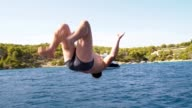 SLO MO Man jumping back somersault into the sea video