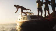 SLO MO Man jumping into water from party boat at sunset video