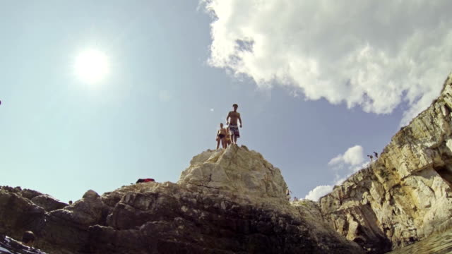 SLOW MOTION: Man jumping of the cliff into the ocean video
