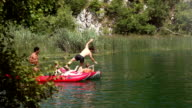 Man jumping off canoe into river, friends laughing video
