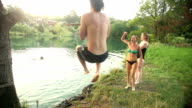 Man jumping off rope swing into river while friends cheer for him video