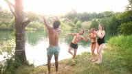 Man jumping off rope swing into river while friends cheering for him video