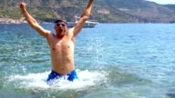 SLO MO Man jumping out of the sea video