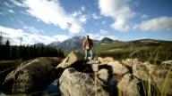 Man jumps rock to rock in mountain lake video