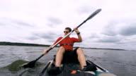 Man kayaking on open water, guy swims in kayak or canoe under dark clouds video