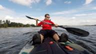 Man kayaking on open water, guy swims in kayak or canoe video