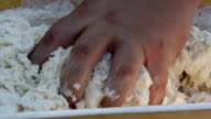 Man kneading dough in a wooden bowl video