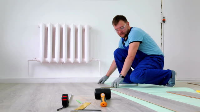 Man Laying floor Laminate indoors video