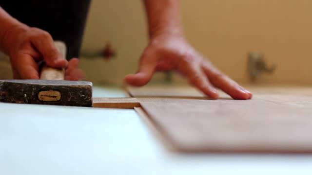 man laying laminate video