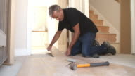 Man laying laminate wood panel flooring in a house video
