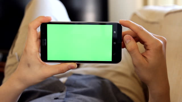 man laying on couch and using mobile phone with green screen in landscape mode video