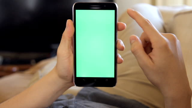 man laying on couch at home and using mobile phone with green screen video