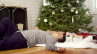 A man lays down under a christmas tree while his wife reads a magazine after a long day video