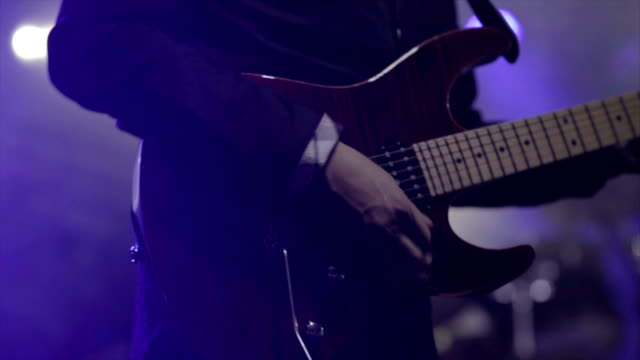 Man lead guitarist playing electrical guitar on concert stage  slow motion video