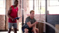 Man learning ropes gym workout with a personal trainer with tablet video