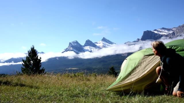 Man leaves tent, looks out to mountains from ridge video