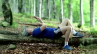 Man lies on a fallen tree in the forest and uses smartphone video
