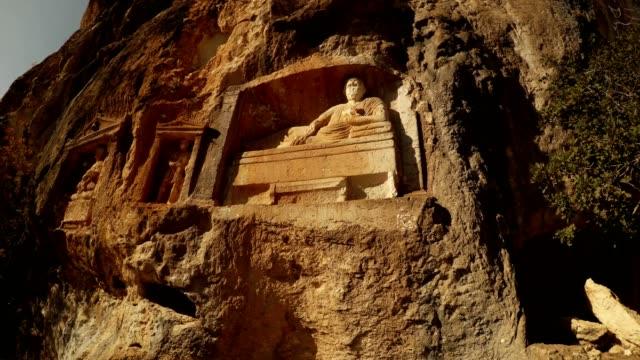 Man lies with bowl in hand  figures in niches Adamkayalar Mersin province Turkey panorama video