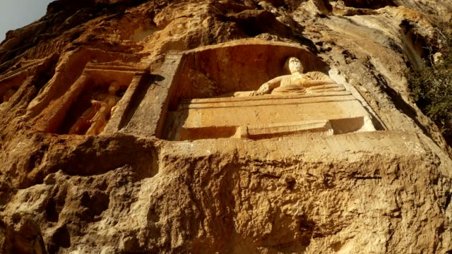 Man lies with bowl in hand  figures in niches Adamkayalar Mersin province Turkey panorama bottom view video