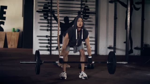 Man lifting barbell in gym video